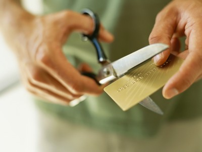 close-up of human hands cutting a credit card by scissors