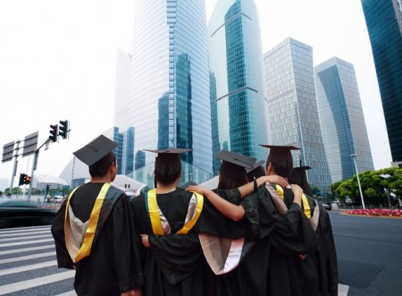 Gui Jun Peng / Shutterstock | http://www.shutterstock.com/pic-112563773/stock-photo-group-of-graduates-will-face-the-modern-city.html