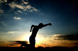 Young adult pumps fist in air during sunset